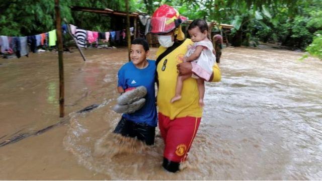 Bomberos rescatan unos niños en Honduras por la crecida del río.
