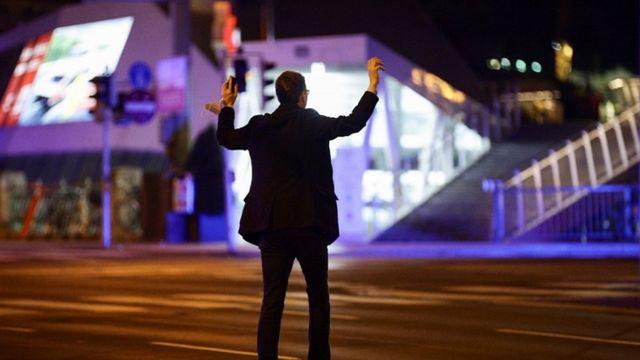 Un hombre levanta sus manos durante inspecciones tras el ataque.