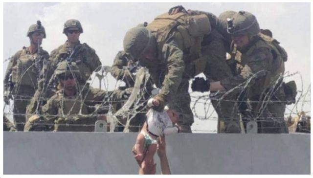 Soldados seguram bebê sendo passada por cima de muro