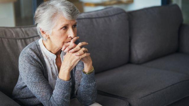 Besorgte Frau auf dem Sofa