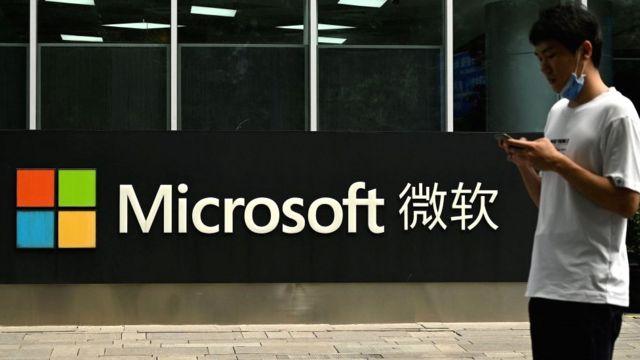 Um homem olha para seu telefone do lado de fora da sede da Microsoft em Pequim em 20 de julho de 2021