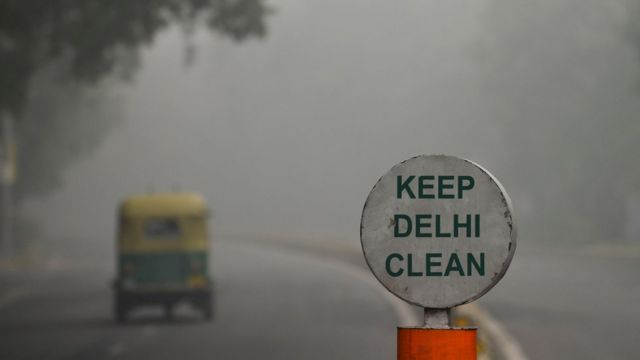 """A sign reading """"Keep Delhi clean"""" with a thick smog in the background"""