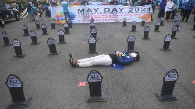 Участник демонстрации в Джакарте, лежащий на асфальте