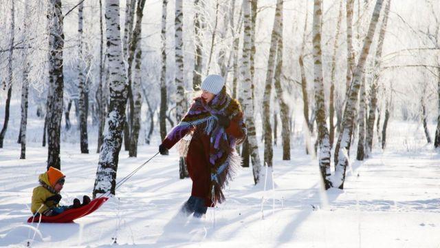Una madre jugando con su hijo en la nieve