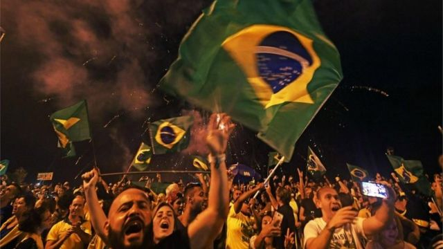 Supporters of far-right lawmaker and presidential candidate for the Social Liberal Party (PSL), Jair Bolsonaro, celebrate in Rio de Janeiro, after the former army captain won Brazil's presidential election, according to official results that gave him 55.7 percent of the vote, on October 28, 2018.