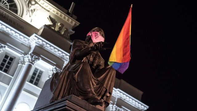 Statue of Copernicus in Warsaw with LGBT flag and pink face mask
