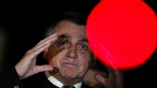 Bolsonaro falando a apoiadores em área externa, à noite, com olhar consternado