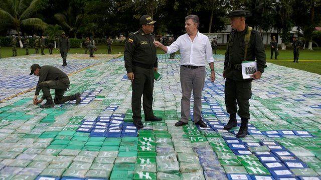 El presidente de Colombia, José Manuel Santos, junto a la policía encargada de la operación mostrando parte de la cocaína incautada en el operativo