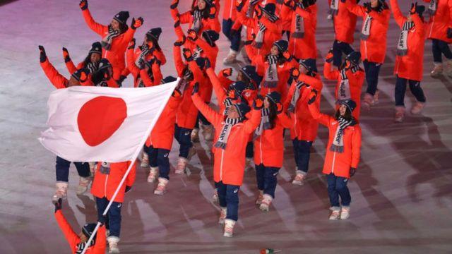 Atletas olímpicos com bandeira do Japão enquanto apresentam delegação