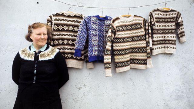 žena pozira, sa džemperima okačenim o zid