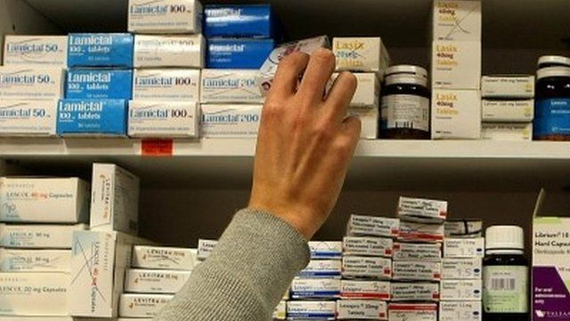 Pharmacist reaching for drugs