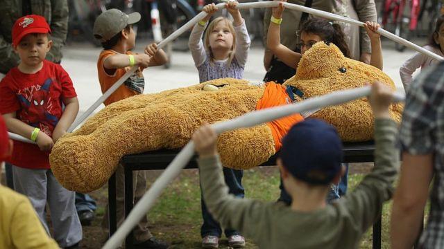 Niños alrededor de un peluche gigante.