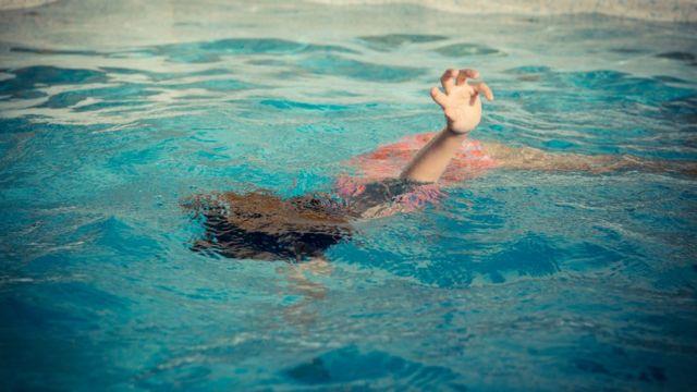 Pessoa na água com o braço levantado