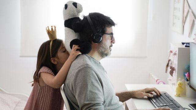 Homem usa o computador, enquanto menina coloca um ursinho de pelúcia em seu pescoço