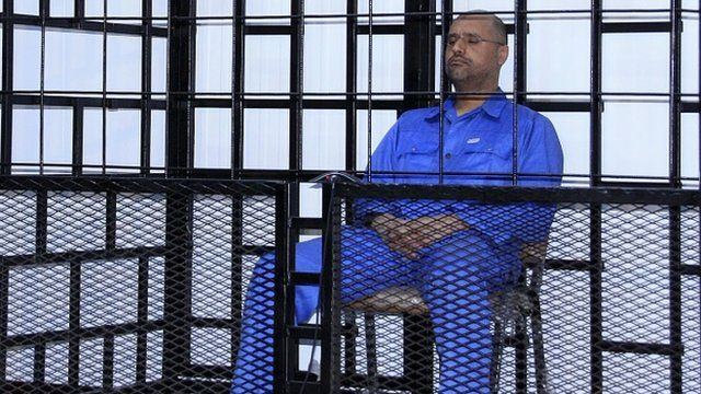 File image from 2014 - Saif al-Islam Gaddafi, son of late Libyan leader Muammar Gaddafi, attends a hearing behind bars in a courtroom in Zintan