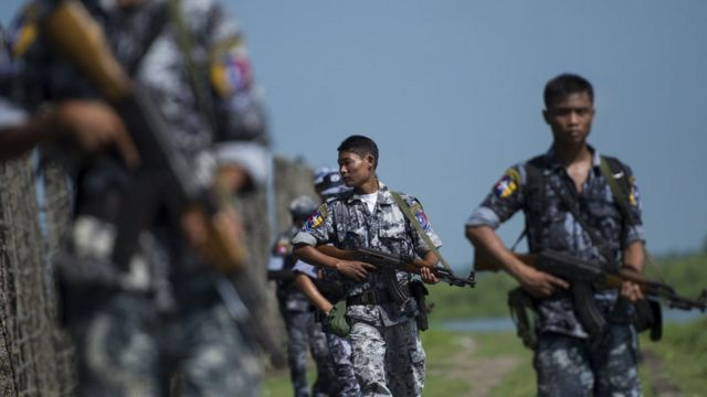 An armed Myanmar border police patrol along a fence by the river dividing Myanmar and Bangladesh border located in Maungdaw, Rakhine State on October 15, 2016
