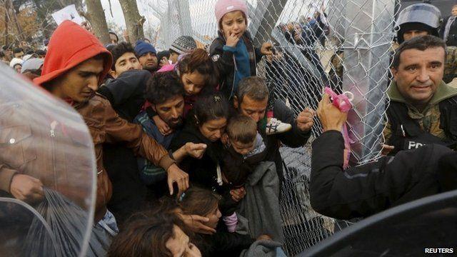 A Syrian refugee family prepares to cross the Greek-Macedonian border through a metal border fence near the village of Idomeni