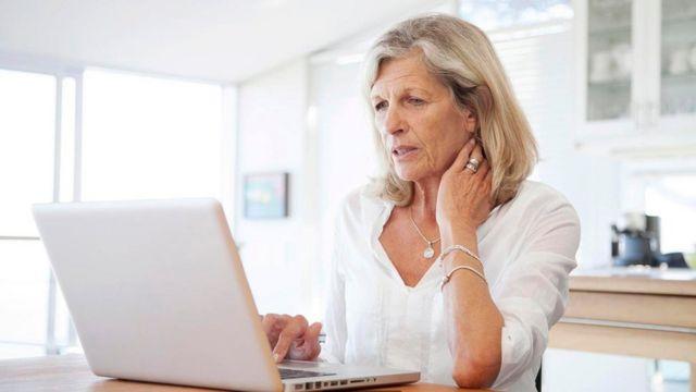 سيدة تقرأ من شاشة كمبيوتر محمول
