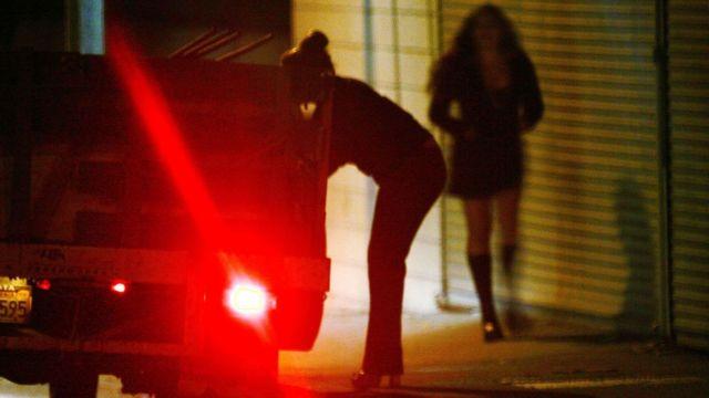 À noite, mulher na calçada se aproxima de carro