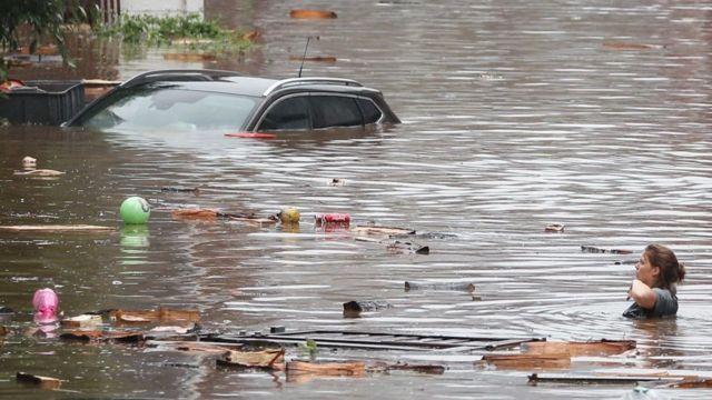 Una mujer intenta moverse en una calle inundada tras las fuertes lluvias en Lieja.