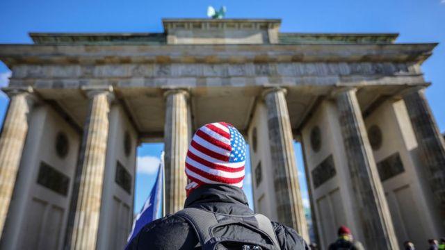 Um homem com um gorro de bandeira dos EUA está parado em frente ao Portão de Brandemburgo