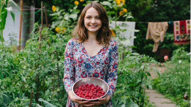 Mulher com frutas vermelhas em um jardim