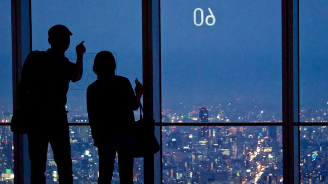 Silhouette of a couple at the 60th floor observatory at the Abeno Harukas building overlooking Osaka, Japan