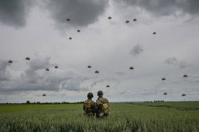 Участники исторической реконструкции наблюдают за высадкой 280 парашютистов во французском Саннервиле.