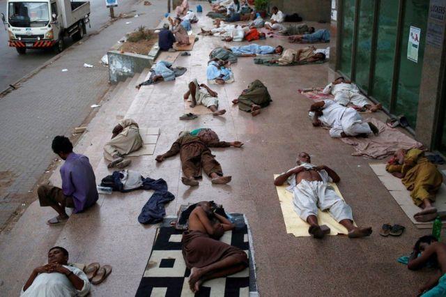 Orang-orang tidur di trotoar untuk menghindari panas dalam ruangan di Karachi, Pakistan.