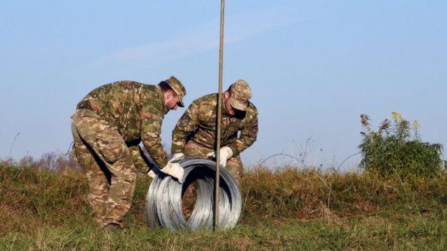 スロベニアとクロアチアの国境で鉄線を設置するスロベニア兵士(11日)