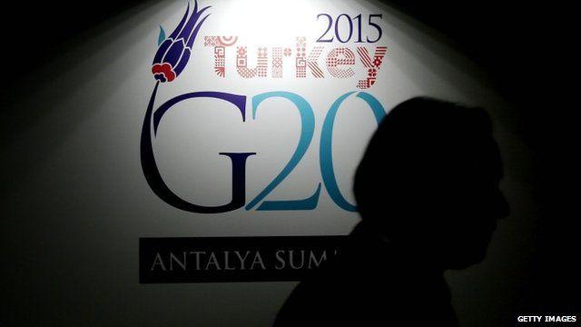 Man walking past G20 sign