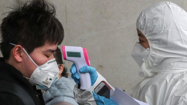 신종 코로나바이러스감염증(코로나19) 확산세가 급증하고 있는 25일 오후 중국인 유학생들이 인천국제공항 입국장을 통해 입국해 대학 관계자로부터 체온 검사를 받고 있다