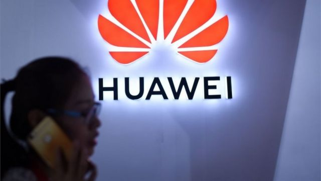 July 8, 2018a woman uses her mobile phone in front of a Huawei logo at Beijing International Consumer Electronics Expo in Beijing.