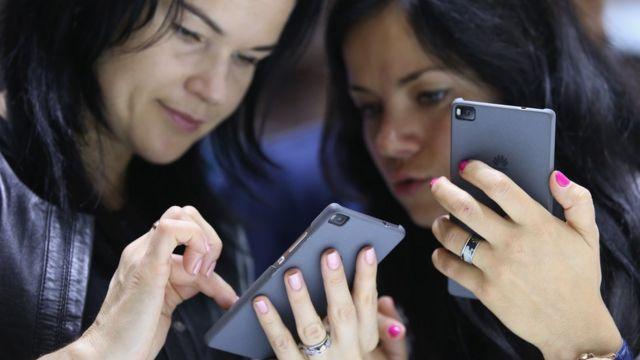 Mujeres con sus teléfonos móviles.