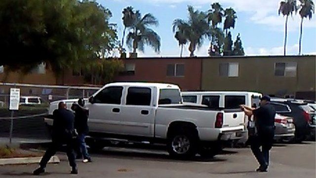 In this video grab courtesy of the El Cajon Police Department and obtained by AFP on September 28, 2016, a man raises his hands as members of the police department approach in El Cajon a suburb of San Diego, California.