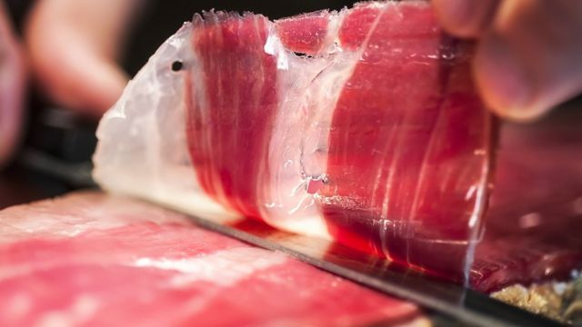 Close up of hand and knife cutting jamon iberico in Spain.