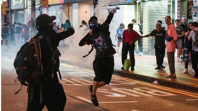 有示威者把警方投擲的催淚彈投回去。