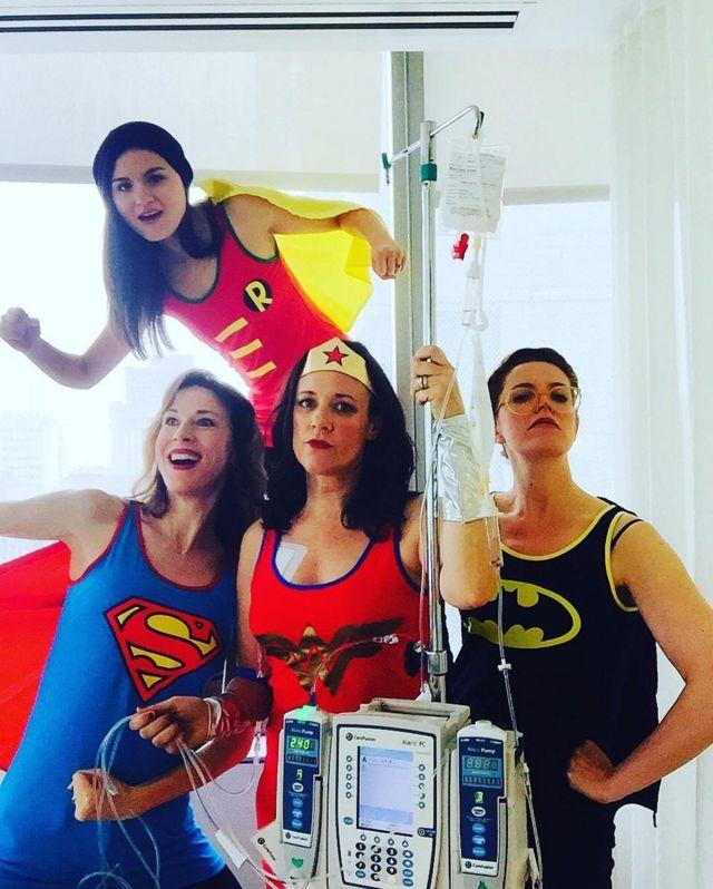 Karen disfrazada como la Mujer Maravilla, rodeada de mujeres disfrazadas de Super Man, Batman y Robin.