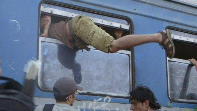 Migrant clambers on board through a narrow window