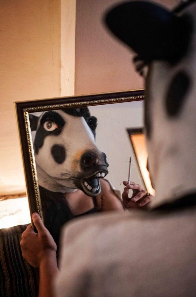 Женщина в маске коровы смотрится в зеркало