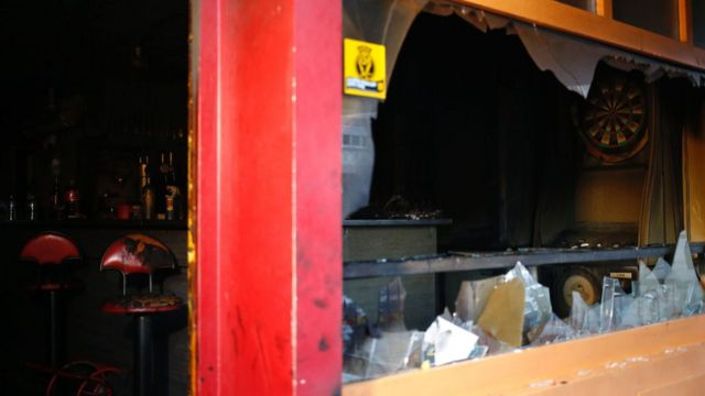 Interior of bar damaged by fire in Rouen - shows broken window, blackened bar stools (6 August 2016)
