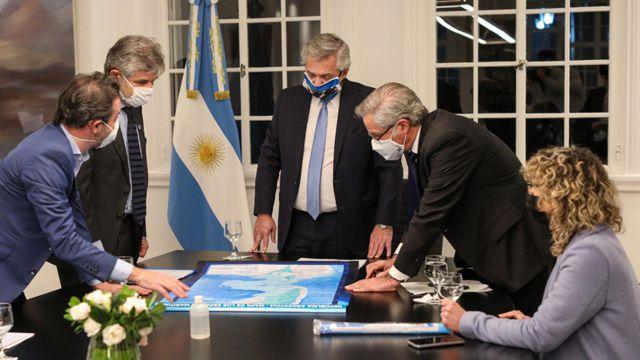 Alberto Fernández (centro) y otros funcionarios, mirando el nuevo mapa de Argentina