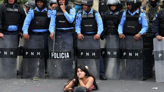 Una manifestantes se acuesta frente a la policía en una protesta contra la reelección del presidente Hernández en Honduras.