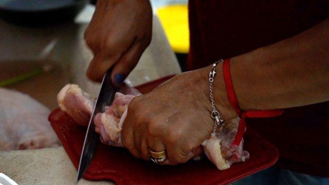 Lindinalva cortando carcaça de frango que comprou perto da casa dela, na zona leste de SP