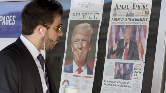 नतीजों के बाद ट्रंप के पोस्टर देखता एक अमरीकी