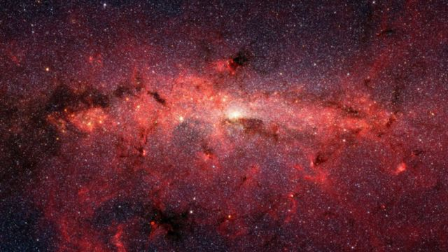 ภาพถ่ายด้วยรังสีอินฟราเรดจากกล้องโทรทรรศน์อวกาศสปิตเซอร์ของนาซา แสดงให้เห็นใจกลางกาแล็กซีทางช้างเผือกที่มีดาวฤกษ์นับหลายแสนดวง