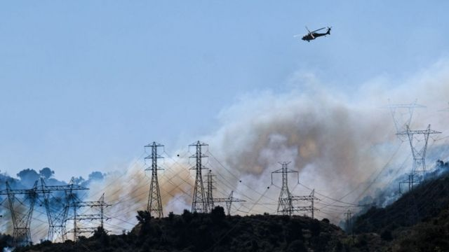 Helicopters fly over power lines engulfed in smoke