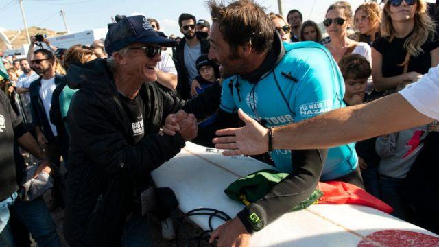 Surfista João De Macedo saluda a seguidores.