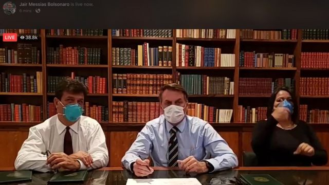 O ministro Luiz Mandetta, o presidente e intérprete de Libras com máscaras durante transmissão ao vivo no Facebook