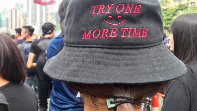 阿依戴帽、戴口罩参加游行,与周围的人讲广东话。